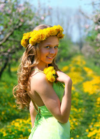 Girl stand in the apple garden with dandelions