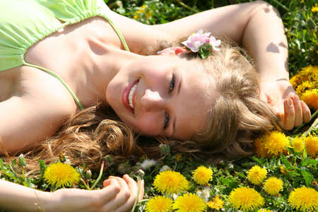 Girl lieing onthe grass with dandelions photo