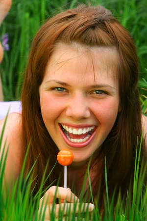 Smiling Girl with orange Lollipop