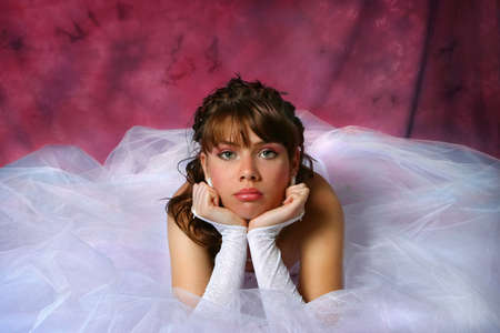 Bride posing on dark red backdrop Stock Photo