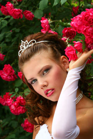 Beauty Girl in Wedding Dress in the red roses Stock Photo