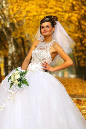 Beautiful Bride posing in autumn park