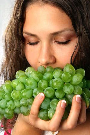 Beautiful Girl eating green grapes photo