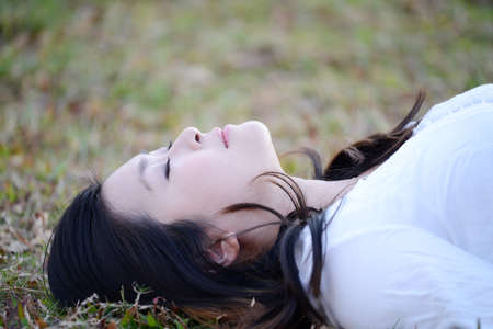 woman laying down: Asian woman laying down on green grass in the park.