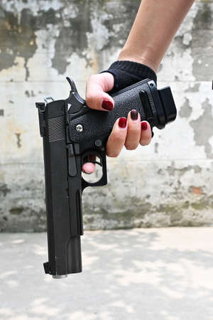 Gun in a hand of a woman on the cement wall.