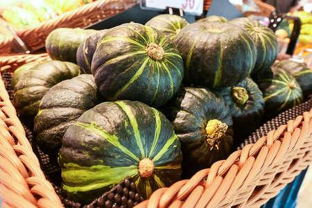 Bunch of Green pumpkins on shelf in a super market. Close-up view.