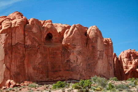 red rock: Cave Formation Arches National Park - A red rock formation with a cave carved out of Entrada Sandstone in Arches National Park near Moab Utah. Stock Photo