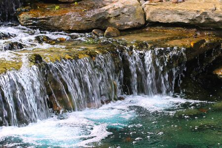garden pond: Pond Water Cascade - A garden pond supports a multi-tiered waterfall with many layers of rock slabs.