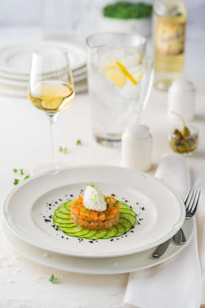 salmon Tartar with cheese souffle on a white plate surrounded by Cutlery and white wine