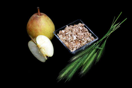 pear, cut apple, wheat and crunches over black background photo
