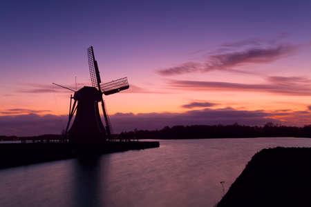 groningen: windmolen silhouet over kleurrijke hemel tijdens zonsondergang in Groningen Stockfoto
