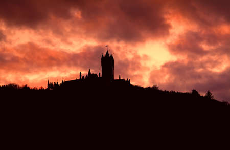 silhouette of the old castle over cloudy sky during sundown photo