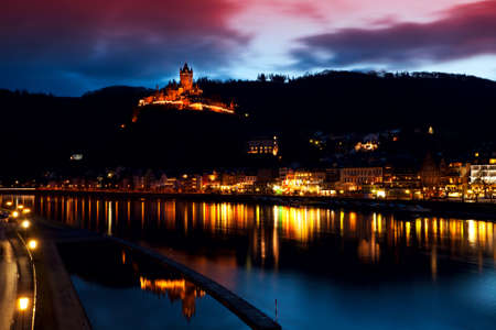 illuminated city and castle close to river in Cochem (Mosel) with long exposure Stock Photo