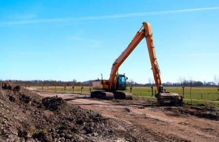 orange excavator with bucket outdoors photo