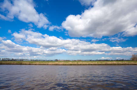 lines of land, water and blue sky with blue puffy clouds photo