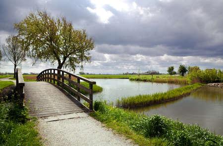 mooie houten kleine brug door de rivier en bewolkte hemel Stockfoto