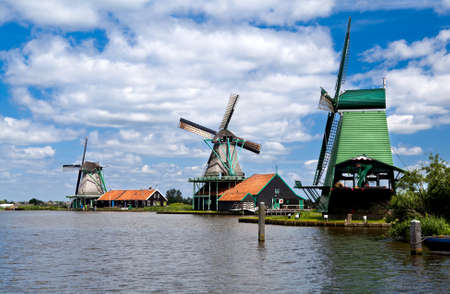 three windmills in Zaanse Schans close to river over beautiful sky photo