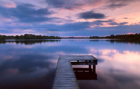 uitzicht vanaf pier op het meer bij zonsondergang