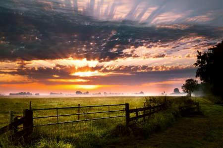 kleurrijke zonsopgang over landelijke weiland in Groningen Stockfoto