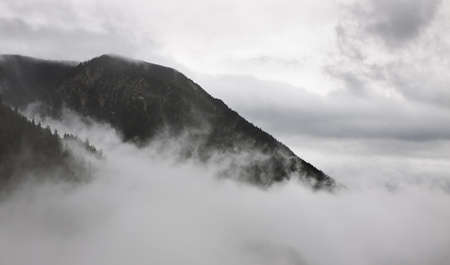 mountain pick in fog in Bavarian Alps photo