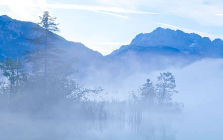 mountains and alpine lake (Barmsee) in early morning fog