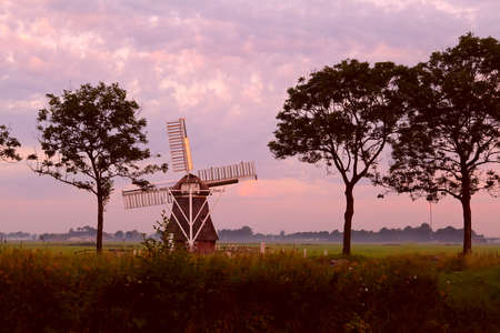 Dutch windmill on field at sunrise photo