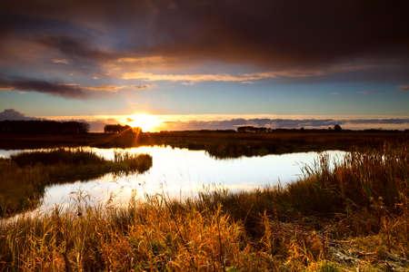 warmen Sonnenstrahlen bei Sonnenaufgang �ber wilde See Leekstermeer, Drenthe schlie�en Lizenzfreie Bilder