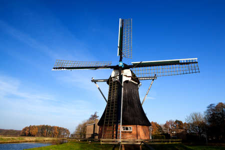 wooden Dutch windmill over clear blue sky photo