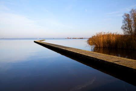 long lake: long wooden pier on big blue lake Stock Photo