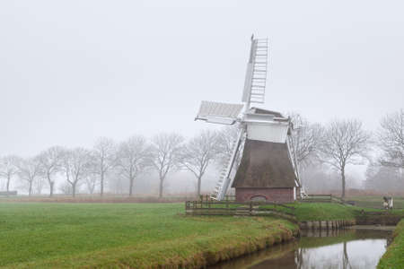 Dutch windmill in dense fog, by canal in Groningen photo