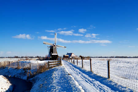 Dutch windmill and farmhouse in snow during winter photo