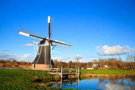 Dutch wooden windmill by lake over blue sky photo