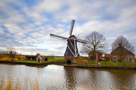 Dutch windmill and farmhouse by canal