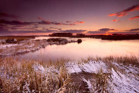 sunrise over wild lake in snowy winter photo