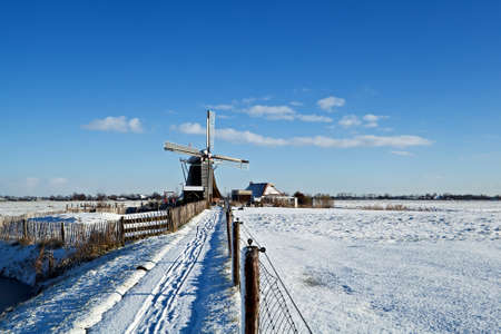 Dutch windmill on meadow during snowy winter photo