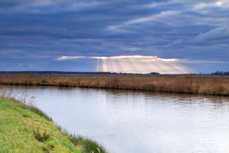 sunbeams through clouded sky during storm over canal photo