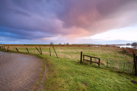 dramatic sunrise over road and fence