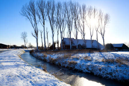 sun over Dutch farm with canal in winter Stock Photo - 17065981