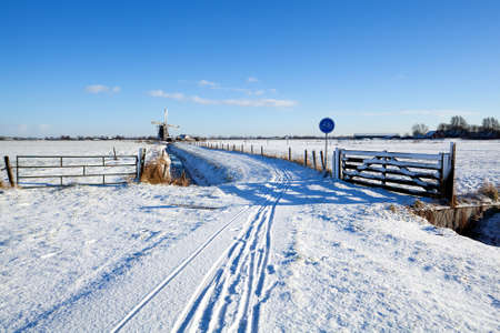bicycle road by Dutch windmill in snowy winter photo