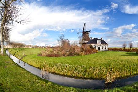Dutch windmill by canal over blue sky Banco de Imagens