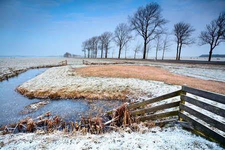 wooden fence and frozen canals in Dutch farmland Stock Photo - 17424351