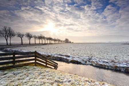 sunrise over snow pasture and canal with fence