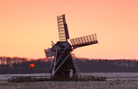Charming Dutch windmill and sun during sunset photo