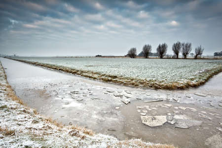 broken ice on frozen river in Dutch winter farmland Stock Photo - 17424405