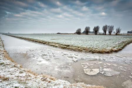 broken ice on frozen river in Dutch winter farmland Stock Photo - 17424405