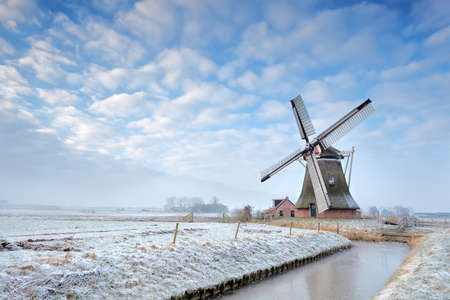 Dutch windmill by canal in winter photo