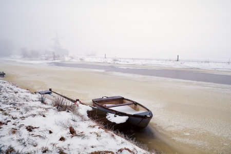 boat on frozen canal in fog,  Netherlands Stock Photo - 17621252