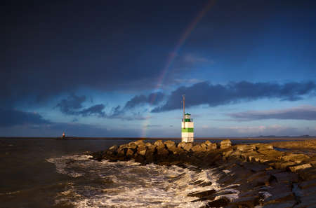 lighthouse and rainbow over North sea after shower photo