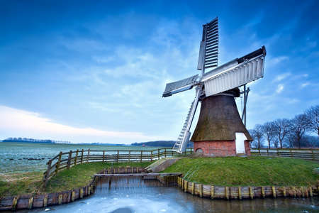 charming Dutch windmill by frozen canal in winter photo