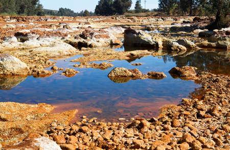 acidic: big stones in acidic river Tinto in Niebla (Huelva), Spain